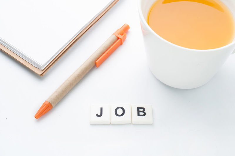whit office table. Beverage Copy Space Apply Background Cup Find Food And Drink Healthy Eating High Angle View Indoors  Job Message Notepaper Ocupation Orange Juice  Pad Paper Pencil Preparation  Presentation Search Studio Shot Text White Background