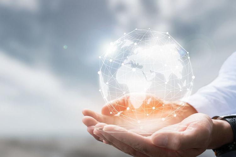 Digital composite image of hands under globe