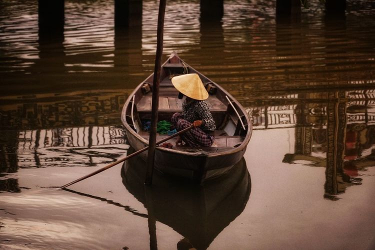 Side view of fisherman wearing asian style conical hat while crouching on fishing boat in lake