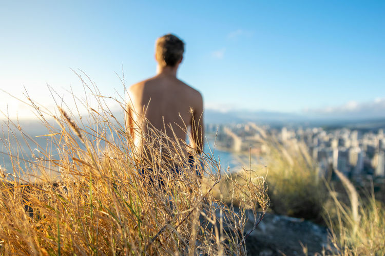 Close-up of grass against shirtless man looking at view from mountain