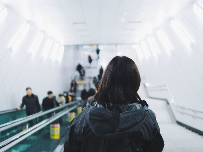 Woman take the escalator down to subway. Background of White subway. White Station People Back Background Seoul South Korea Light Clean Background Clean Clear Warm Clothing City Crowd Airport Incidental People Escalator Subway Station Subway Platform Subway Train Passenger
