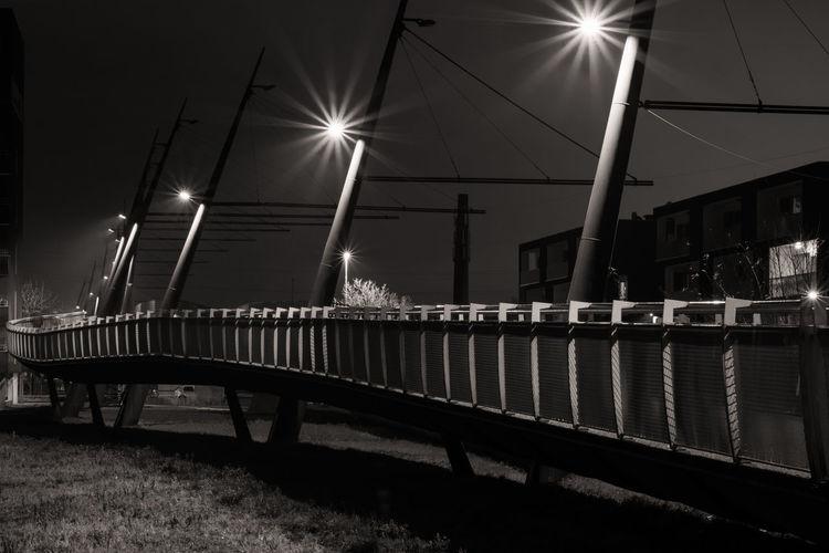 Illuminated street lights against bridge in city at night