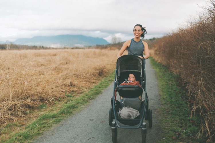 Smiling mother with baby walking on road