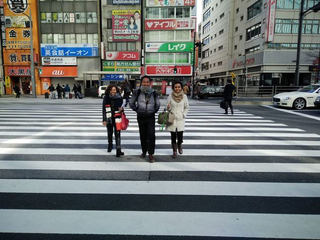 Three Indonesian people crossing the street in Tokyo Architecture Building Built Structure City City Life City Street Day Group Of People Information Sign Leisure Activity Lifestyles Medium Group Of People Outdoors Pedestrian Road Sign