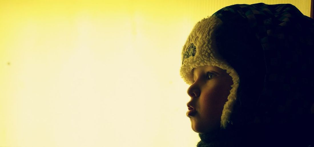 Side View Of Child Wearing Hunters Cap Against Clear Sky During Winter