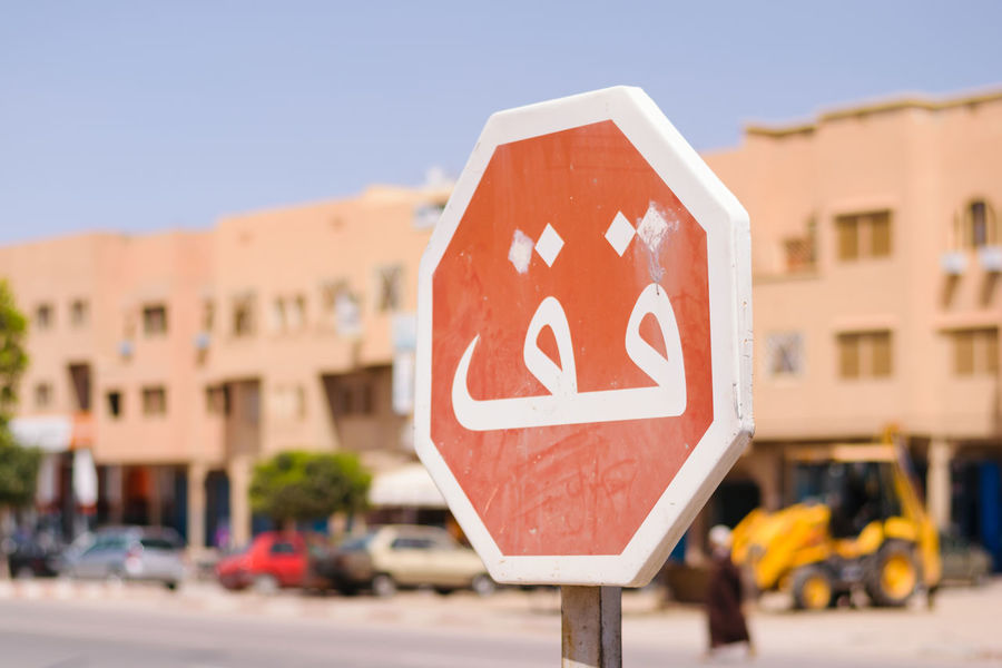 Image of a stop sign in focus and a blurred background whith arabic script in Morocco. Arabic Script Red Arabic Language City Day Focus On Foreground No People Outdoors Road Sign Stop Stop Sign Transportation