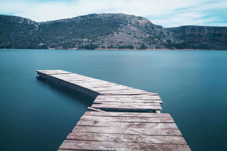 wooden pier or jetty on lake. Photo taken with long exposure time to create a silky water effect. Pier Jetty Long Exposure Water Nature Blue Outdoors Lake River Blue Sky Cloud Color SPAIN The Great Outdoors - 2016 EyeEm Awards The Essence Of Summer Landscape Silky Beautiful Abstract Seascape Market Reviewers' Top Picks