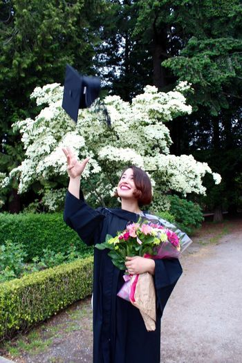 Happy woman in graduation gown throwing mortarboard while standing against plants