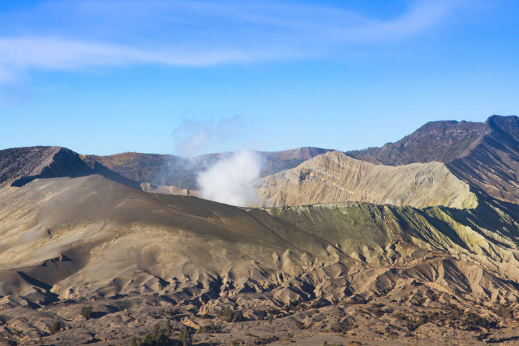 Scenic view of volcanic landscape against blue sky