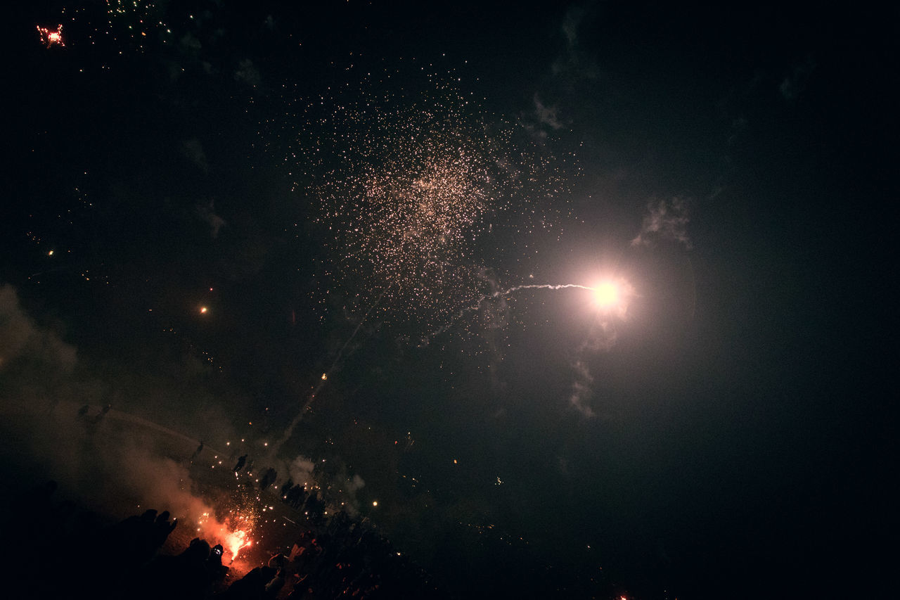 night, glowing, firework display, outdoors, celebration, smoke - physical structure, low angle view, illuminated, burning, event, no people, firework - man made object, sky, arts culture and entertainment, motion, nature