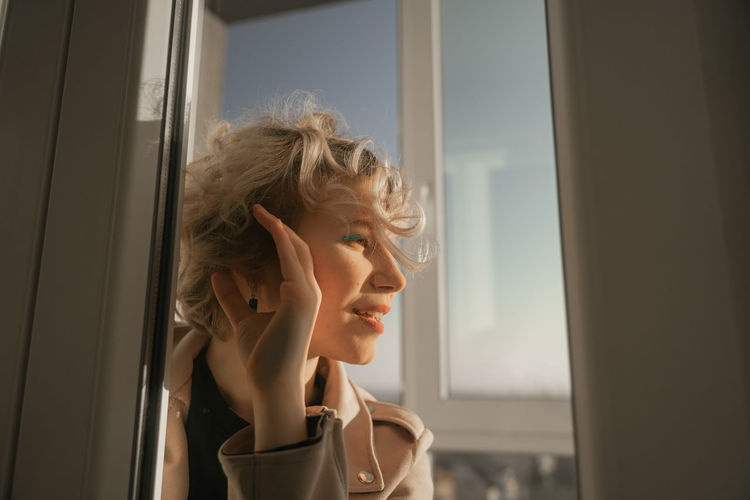 Portrait of smiling woman sitting by window at home
