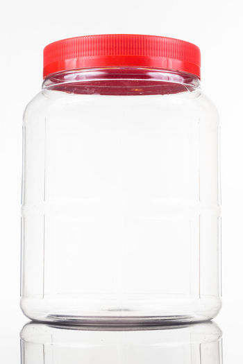 Plastic jar bottle with red cover lid against white background Bottle Close-up Container Copy Space Cover Cut Out Food And Drink Glass - Material Healthcare And Medicine Indoors  Lid No People Plastic Polyurethane Red Color Single Object Still Life Studio Shot Transparent White Background White Color