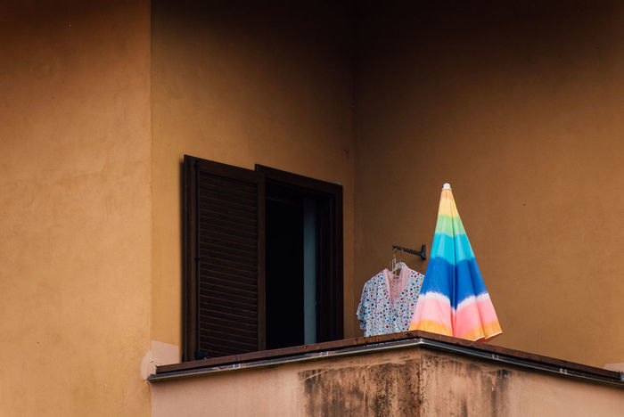 Architecture Balcony Bathrobe Building Exterior Built Structure Day Dressing Gown Flag Housecoat Lgbt Low Angle View No People Outdoors Parasol Patriotism Rainbow Robe Sunshade Umbrella Window