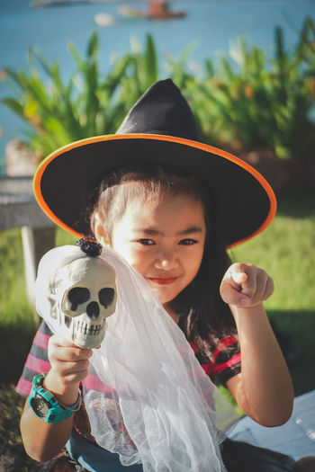 My little witch, Halloween day.. Cosplay Halloween Sunlight Asian Girl Black Hair Celebration Child Childhood Clothing Day Emotion Females Focus On Foreground Front View Girl Happiness Hat Holding Innocence Kid Leisure Activity Lifestyles Little Girl Looking At Camera Magic One Person Outdoors Playful Portrait Pre-adolescent Child Real People Skull Smiling Smilling Witch Wonder Young Adult
