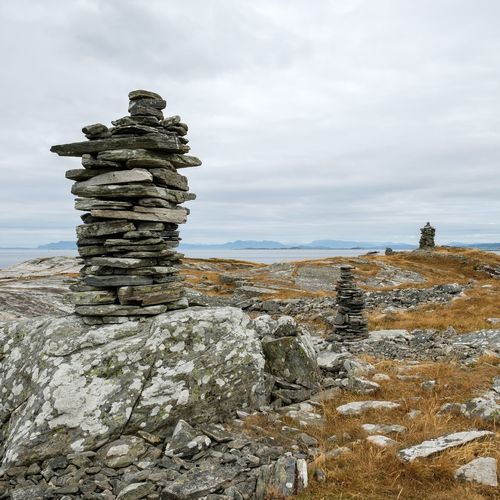 some weathered piles of stone on the norvegian westcoast Beach Stack Sea Water Sky Cloud - Sky Rock Formation Eroded Geology Rugged Stack Rock Rocky Coastline Shore Coast Tranquil Scene Natural Landmark Countryside
