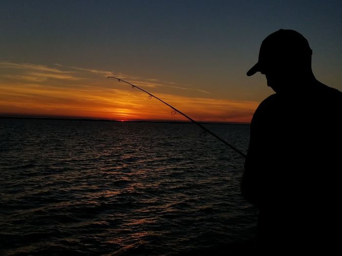 Silhouette mature man fishing in sea against sky during sunset