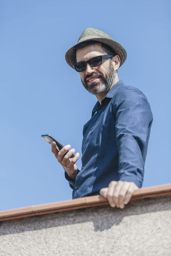 Low angle view of man using smart phone against clear sky