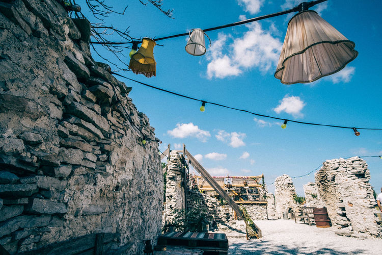 Low angle view of light decorations hanging by stone walls against sky
