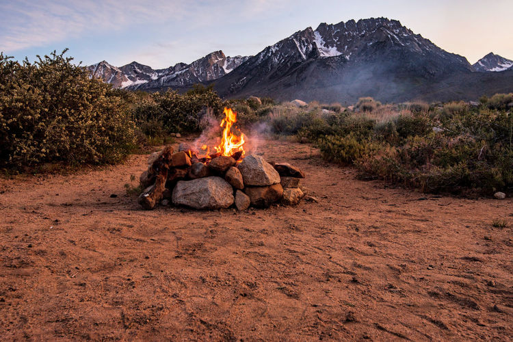 Campsite fire in stone firepit on desert plain at base of mountain