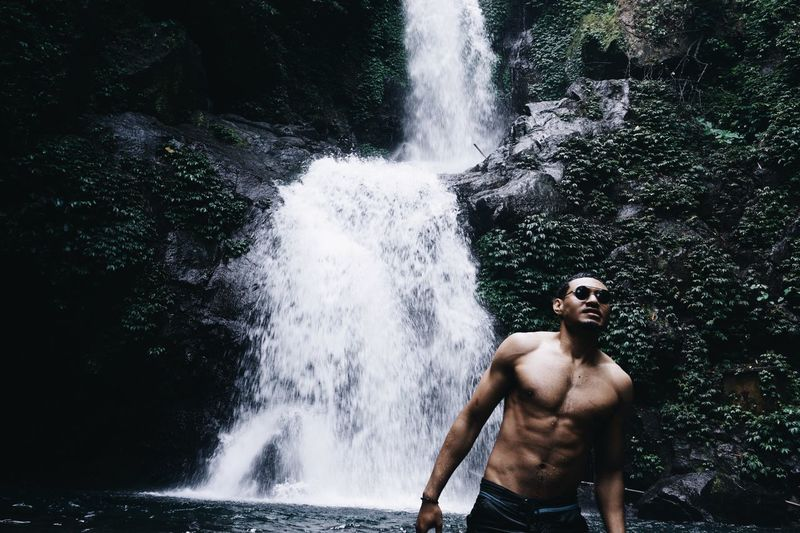 Shirtless man standing against rock and waterfall