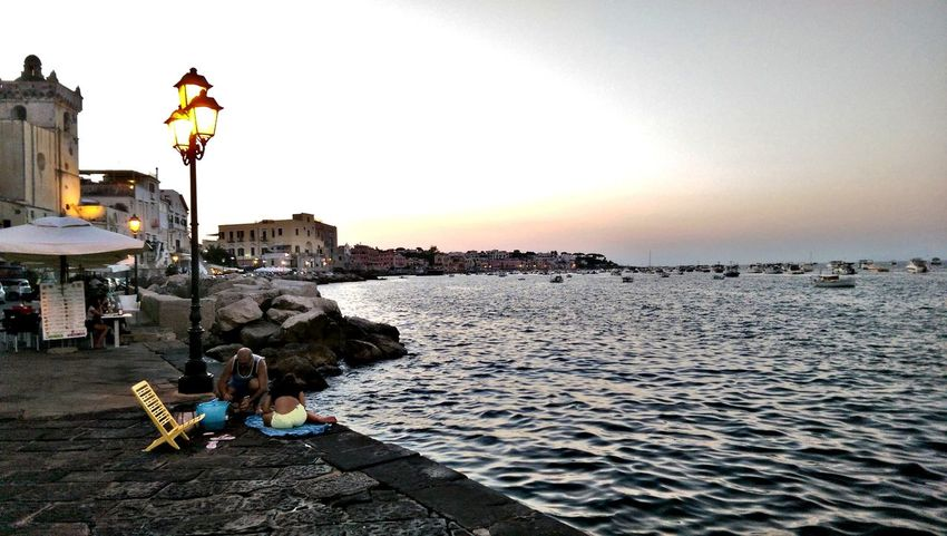 People And Places Sitting Sunset Water Men Street Light City Building Exterior Orange Color Togetherness Weekend Activities City Life In Front Of Distant Tranquility Enjoying Life Ischia Island