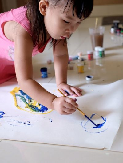 High angle view of girl painting on floor