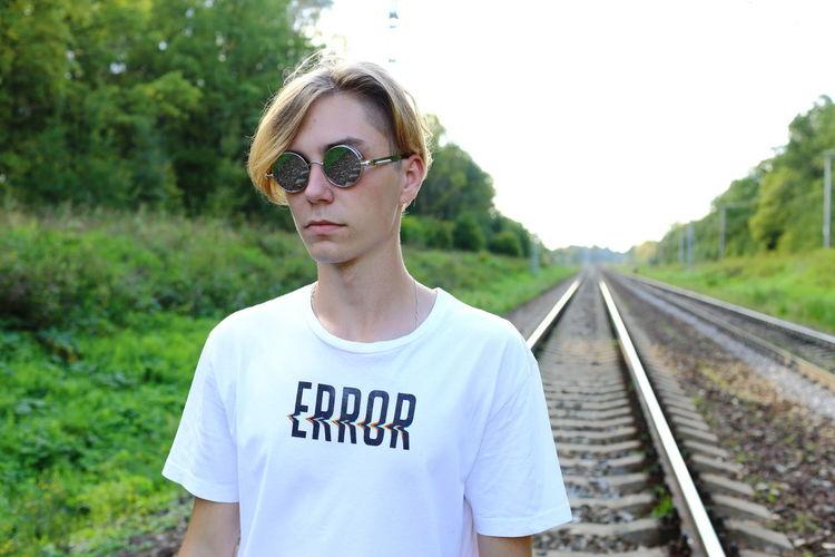 Portrait of teenage boy wearing sunglasses at railroad tracks