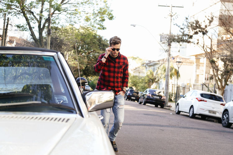 Man Wearing Plaid Shirt And Sunglasses While Walking On Road