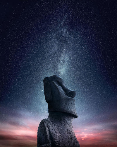 Low angle view of moai statue on mountain against starry sky at night