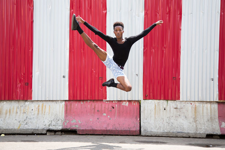Full length of man jumping against corrugated iron