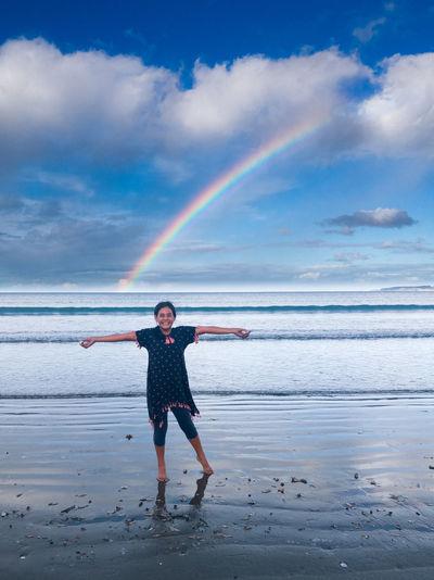 Full length of girl at beach with rainbow