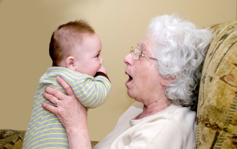 Grandmother making faces at a baby boy trying to get him to smile