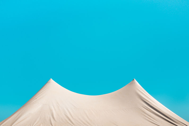 Low angle view of tent against blue sky