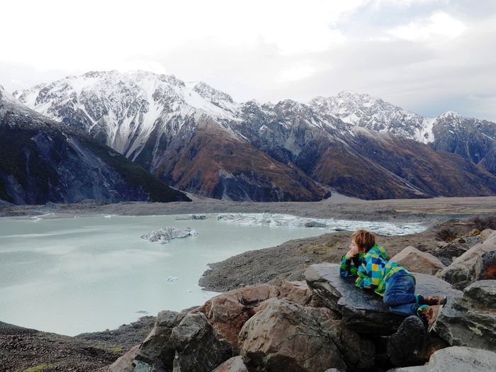 Boy lying on rock by lake against mountain range
