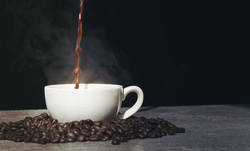 Coffee pouring to cup with coffee bean on black background Cup Coffee Food And Drink Coffee - Drink Drink Mug Indoors  Refreshment Heat - Temperature Coffee Cup Close-up Hot Drink Freshness Roasted Coffee Bean Flame Burning Black Background Food Tea Cup Pouring