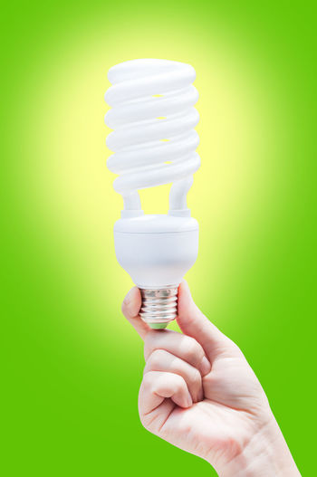 Energy saving concept. Woman hand holding light bulb on green background Body Part Close-up Colored Background Electricity  Energy Efficient Energy Efficient Lightbulb Finger Green Background Green Color Hand Holding Human Body Part Human Hand Indoors  Light Bulb Lighting Equipment One Person Real People Spiral Studio Shot Unrecognizable Person