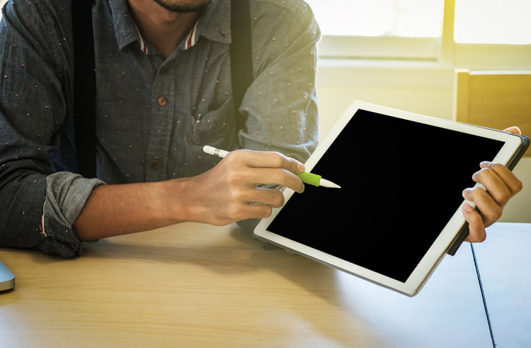 Business Planning Tablet Working Casual Clothing Close-up Connection Executive  Finance Holding Human Hand Indoors  Investment Leadership Male Manager Marketing One Person People Pointing Presentation Real People Sitting Technology Young Adult