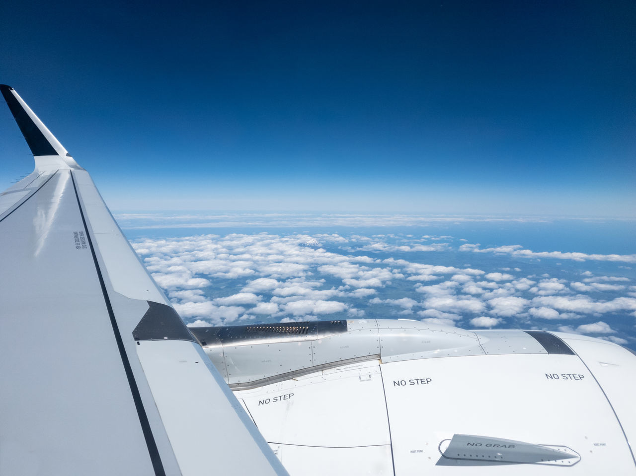 AERIAL VIEW OF AIRPLANE FLYING OVER CLOUDS