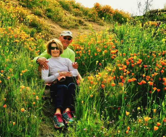 Full length of friends on flower field