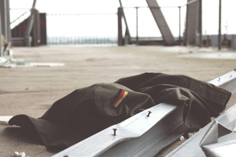 Abandoned Jacket Beside Girders In Courtyard