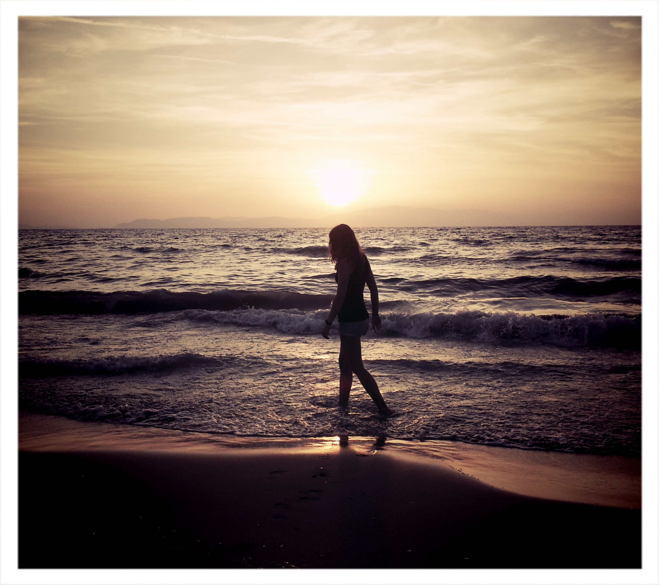 sea, horizon over water, sunset, beach, water, shore, sky, silhouette, leisure activity, scenics, orange color, full length, lifestyles, sun, beauty in nature, tranquil scene, wave, tranquility