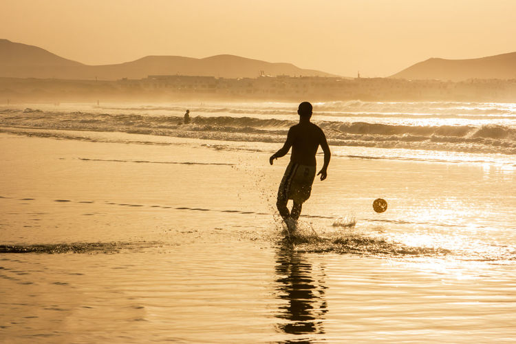 Silhouette man with ball on beach against sky during sunset