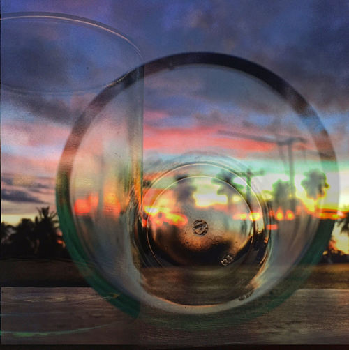 Digital composite image of glass against cloudy sky