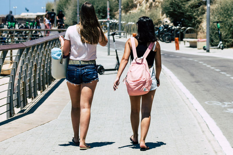 Rear view of women walking on footpath in city