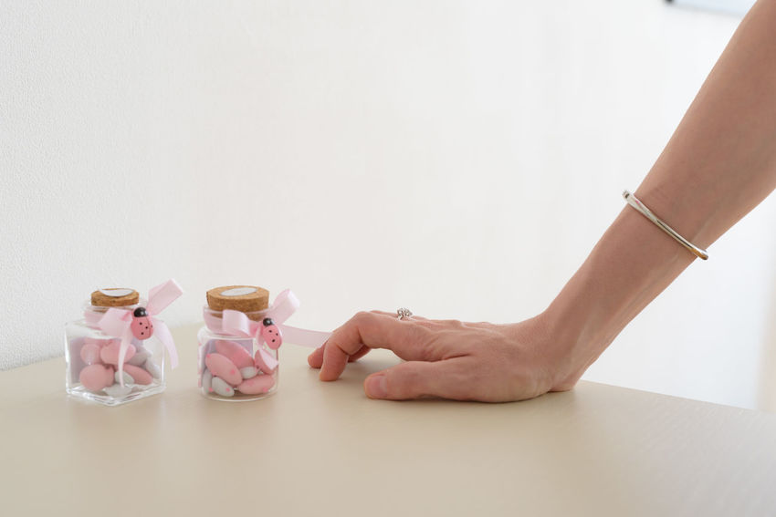 Sugared almonds for christening day Almond Sugared Almonds Ladybug Bottle Christening Day Close-up Container Copy Space Hand Human Body Part Human Hand Indoors  Jar Lifestyles One Person Real People Studio Shot White Background