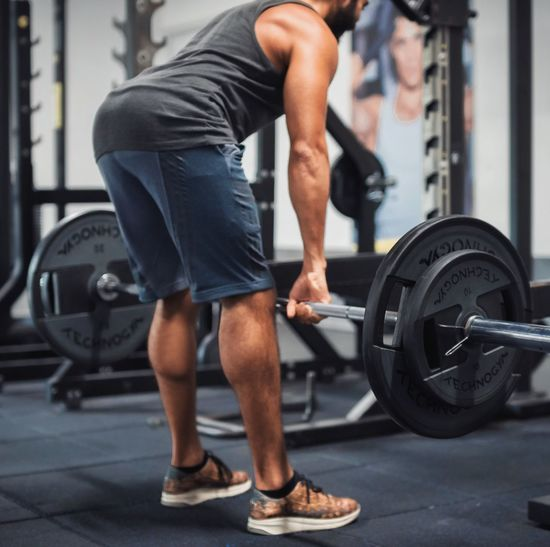 Low section of young man lifting dumbbell in gym