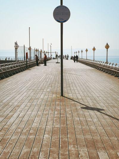 Street lights on footpath by sea against clear sky