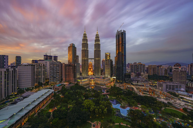 Petronas Twin Towers (fondly known as KLCC) and the surrounding buildings at dramatic sunset seen from the Skybar at Traders Hotel. Dramatic Sky KLCC Park Suria KLCC Architecture Building Exterior Built Structure City Cityscape Cloud - Sky Day Headquarters Illuminated Klcc Modern Moving Clouds Nature No People Outdoors Petronas Twin Towers Sky Skyscraper Tall - High Travel Destinations Tree Urban Skyline