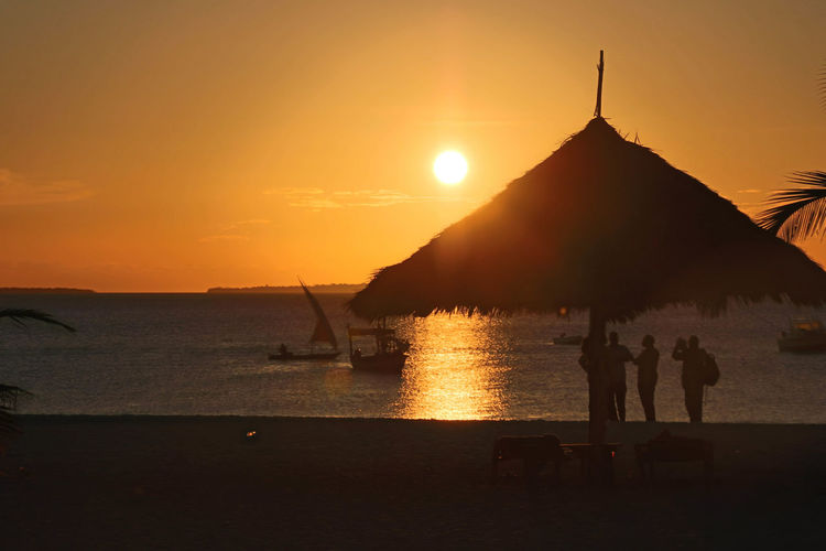 Sunset in Nungwi Zanzibar Beach Beauty In Nature Day Nature Outdoors Real People Reflections In The Water Scenics Sea Silhouette Sky Sun Sunset Thatched Roof Tranquil Scene Tranquility Vacations Water Women