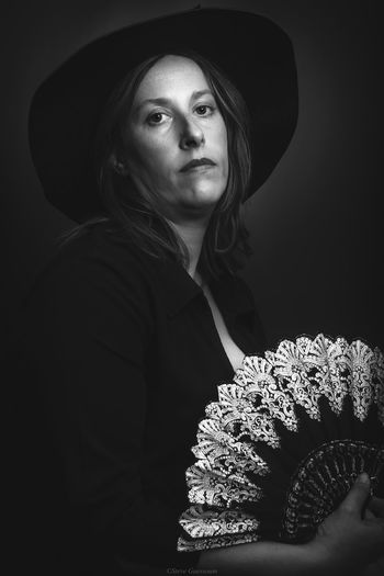 Portrait of woman wearing hat holding folding fan standing against black background